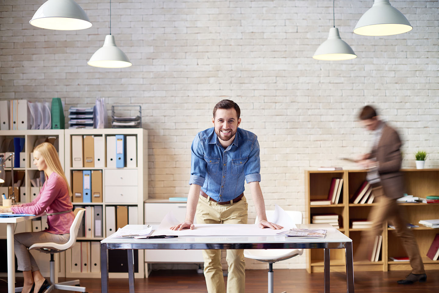 Young designer leaning on table and smiling at camera, his colleagues are busy with work
